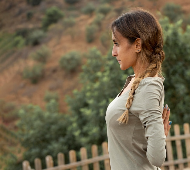Zijaanzicht van de vrouw buiten in de natuur die yoga doet
