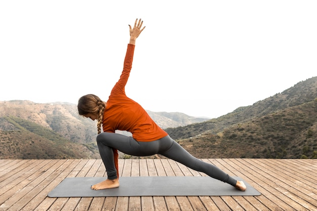 Zijaanzicht van de vrouw buiten in de natuur doet yoga op de mat
