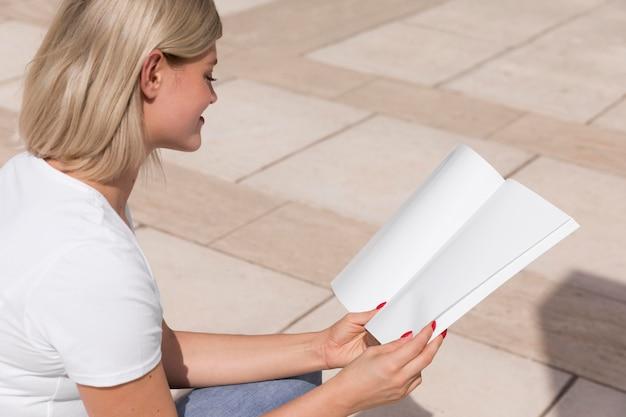Zijaanzicht van de vrouw buiten zitten en boek lezen