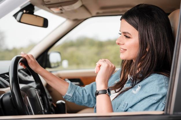 Zijaanzicht van de vrouw die alleen reist met de auto
