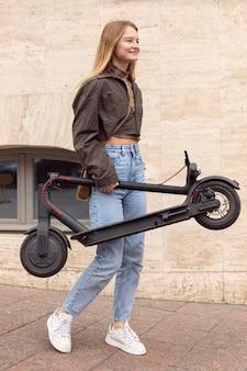 Zijaanzicht van de vrouw die buitenshuis elektrische scooter houdt