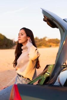 Zijaanzicht van de vrouw die de natuur bewondert vanuit de kofferbak van haar auto