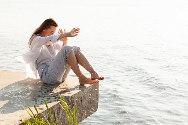 Zijaanzicht van de vrouw die door meerwater wordt bespat