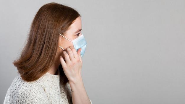 Zijaanzicht van de vrouw die een medisch masker gebruikt voor bescherming met exemplaarruimte