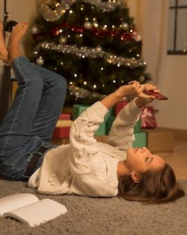 Zijaanzicht van de vrouw die een selfie op kerstmis neemt