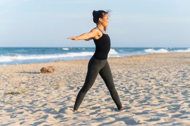 Zijaanzicht van de vrouw die fitness op het strand doet