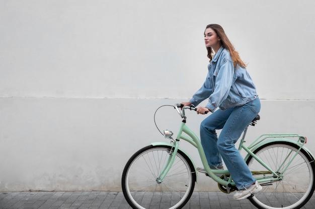 Zijaanzicht van de vrouw die haar fiets berijdt
