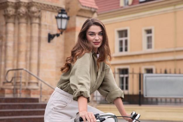 Zijaanzicht van de vrouw die haar fiets in de stad berijdt