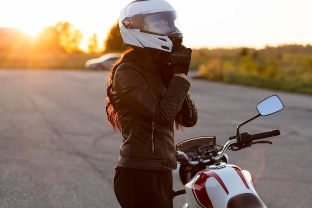 Zijaanzicht van de vrouw die haar helm naast motorfiets opstijgt