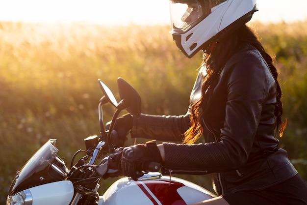 Zijaanzicht van de vrouw die haar motorfiets met helm berijdt
