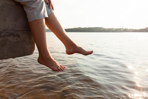 Zijaanzicht van de vrouw die haar voeten aan het meer rust