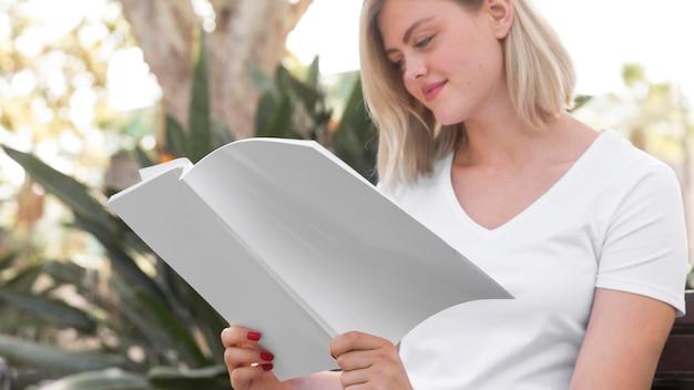 Zijaanzicht van de vrouw die in openlucht boek leest