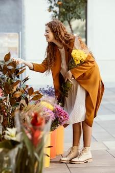 Zijaanzicht van de vrouw die lentebloemen boeket kiezen
