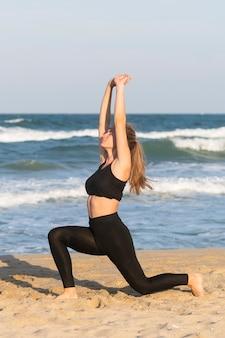 Zijaanzicht van de vrouw die lunges op het strand doet