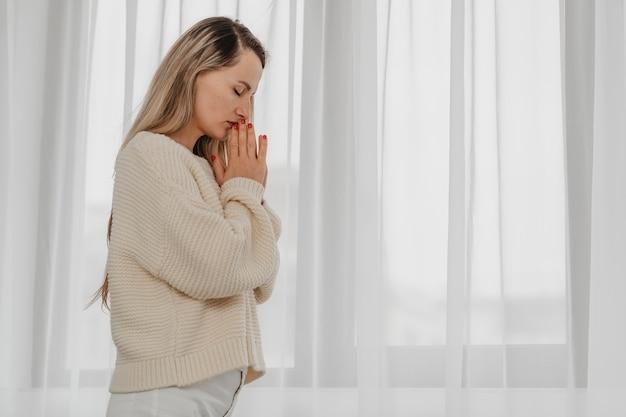 Zijaanzicht van de vrouw die met exemplaarruimte bidt