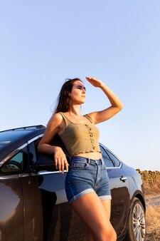 Zijaanzicht van de vrouw die naar de zon kijkt terwijl het rusten op auto