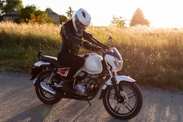 Zijaanzicht van de vrouw die op een motorfiets rijdt