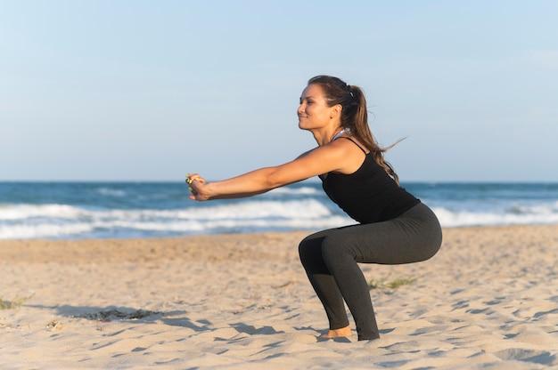 Zijaanzicht van de vrouw die op het strand uitwerkt