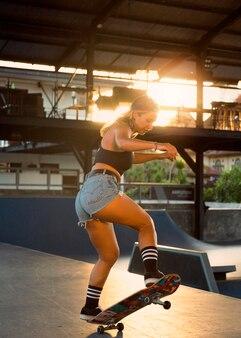Zijaanzicht van de vrouw die skateboarden beoefent