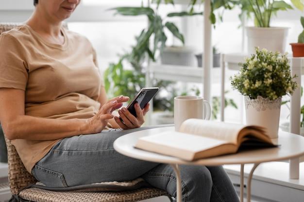 Zijaanzicht van de vrouw die smartphone binnenshuis gebruikt