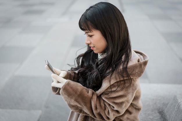 Zijaanzicht van de vrouw die smartphone buitenshuis gebruikt
