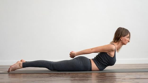 Zijaanzicht van de vrouw die thuis yoga doet