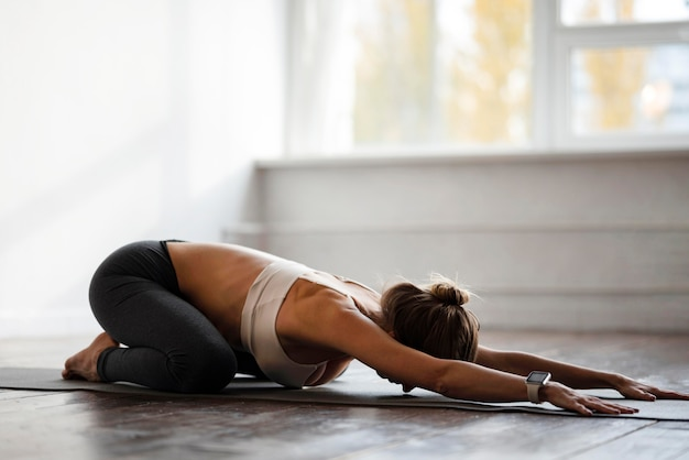 Zijaanzicht van de vrouw die thuis yoga met exemplaarruimte doet