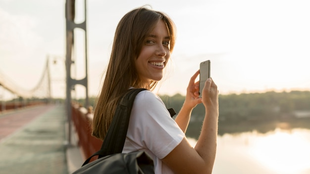 Zijaanzicht van de vrouw die tijdens het reizen foto's van het uitzicht maakt