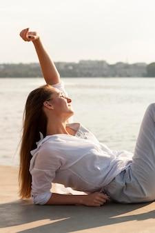 Zijaanzicht van de vrouw die van de zon naast het meer geniet