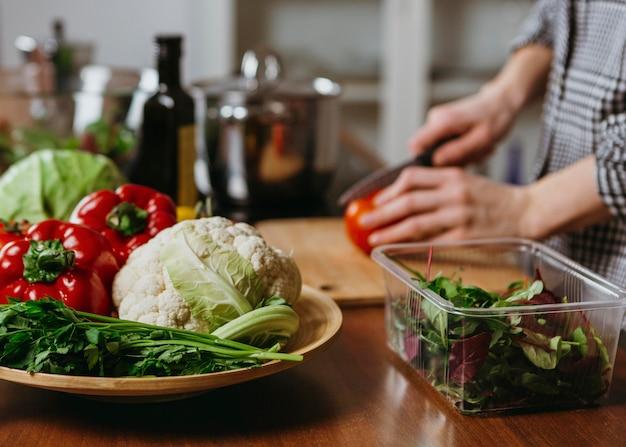 Zijaanzicht van de vrouw die voedsel in de keuken voorbereidt