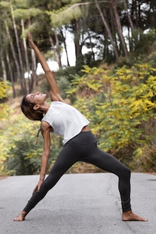 Zijaanzicht van de vrouw die yoga op de weg buiten doet