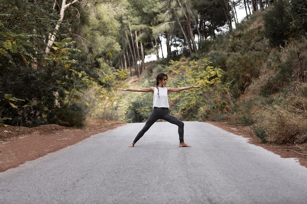 Zijaanzicht van de vrouw die yoga op de weg doet