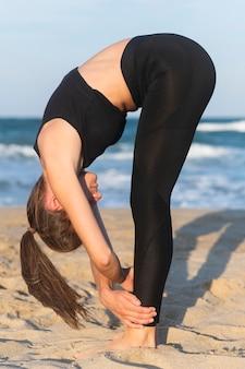Zijaanzicht van de vrouw die yoga op het strand doet