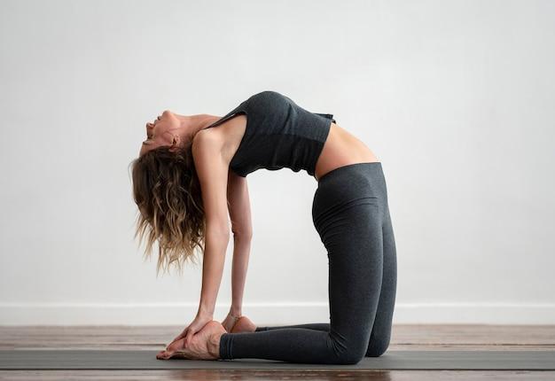 Zijaanzicht van de vrouw die yoga op mat thuis doet