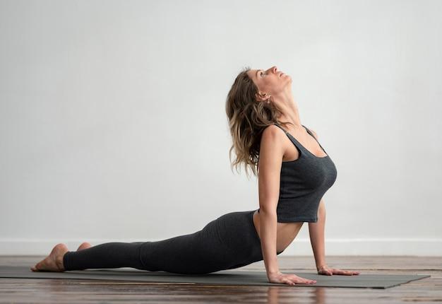 Zijaanzicht van de vrouw die yoga thuis met exemplaarruimte doet
