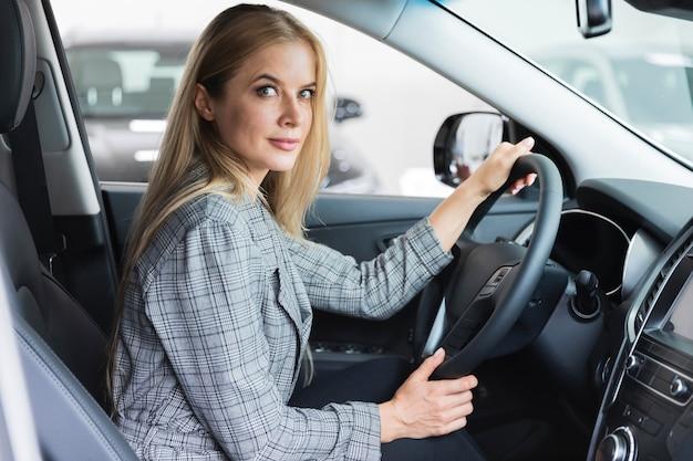 Zijaanzicht van de vrouw in bestuurdersstoel