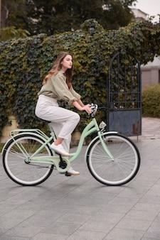 Zijaanzicht van de vrouw in de stad die een fiets berijdt