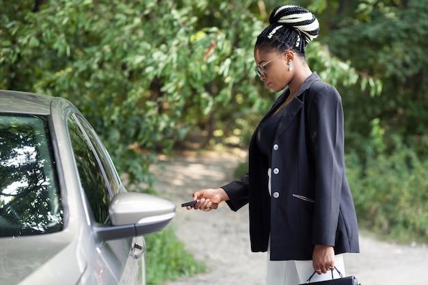 Zijaanzicht van de vrouw met behulp van de sleutels tot haar gloednieuwe auto
