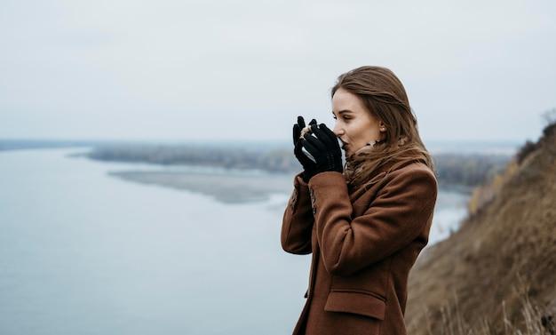 Zijaanzicht van de vrouw met een warme drank aan het meer