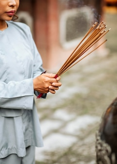 Zijaanzicht van de vrouw met het branden van wierookbundel bij de tempel