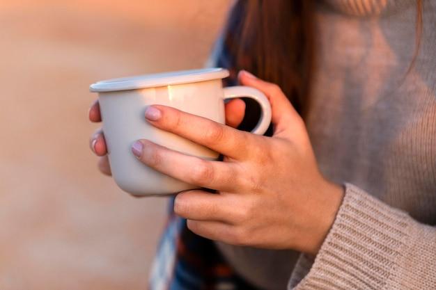Zijaanzicht van de vrouw met kopje koffie terwijl buiten in de natuur