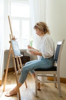 Zijaanzicht van de vrouw met krullend haar thuis schilderen