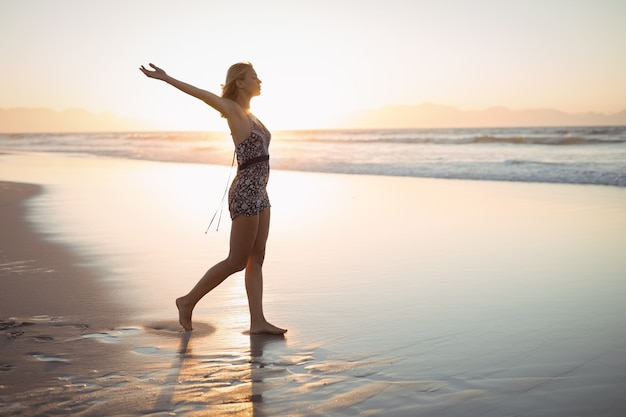 Zijaanzicht van de vrouw met uitgestrekte armen staande op het strand