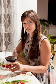 Zijaanzicht van de vrouw met wijn aan tafel