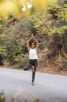 Zijaanzicht van de vrouw op de weg die yoga doet