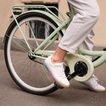 Zijaanzicht van de vrouw op haar fiets in de stad