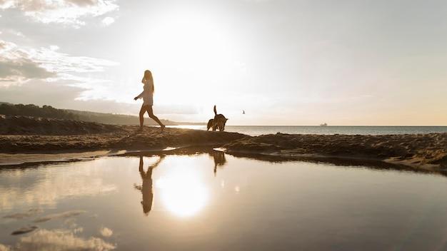 Zijaanzicht van de vrouw op het strand bij zonsondergang