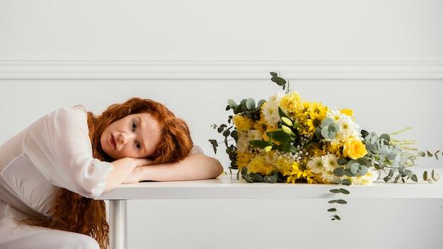 Zijaanzicht van de vrouw poseren met boeket van lentebloemen op tafel