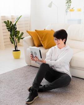 Zijaanzicht van de vrouw thuis met tablet