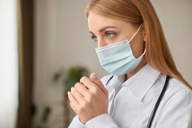 Zijaanzicht van de vrouwelijke arts van het covid-herstelcentrum met het medische masker bidden